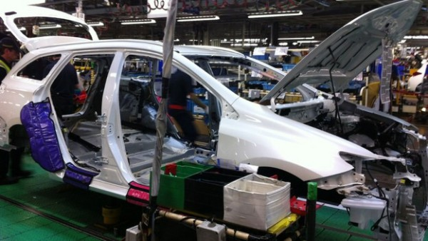 An Auris Touring Sports shell leaves the press and paint facility and joins the assembly track.